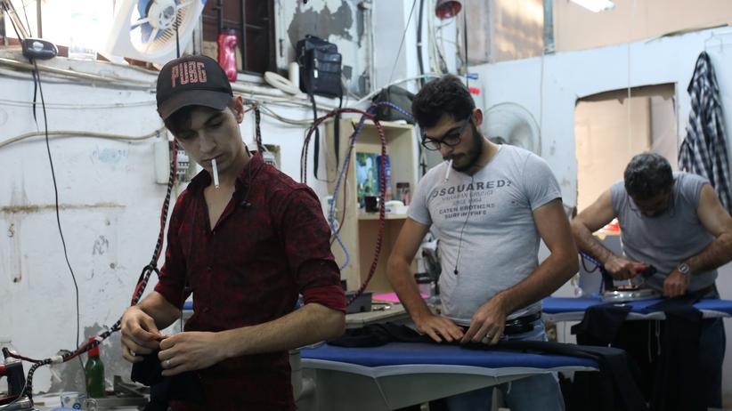 Flüchtlingspolitik: Syrische Männer arbeiten in einem Textilbetrieb in Istanbul. Die türkische Polizei durchkämmt zurzeit viele Betriebe auf der Suche nach Syrern, die sie zur Rückkehr zwingen kann.