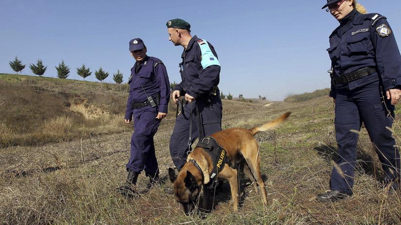 """EU-Agentur: Das Symbolbild zeigt griechische Grenzschutzbeamte und einen Beamten von Frontext. Die von """"report München"""" ausgewerteten Dokumente sollen unter anderem belegen, dass es auch zu """"Hetzjagden mit Hunden"""" gekommen war."""