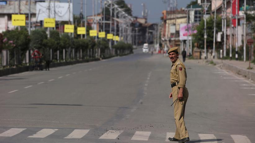 Kaschmir-Konflikt: Ein indischer Polizist überquert eine leere Straße, nachdem der Region der Autonomiestatus entzogen wurde.