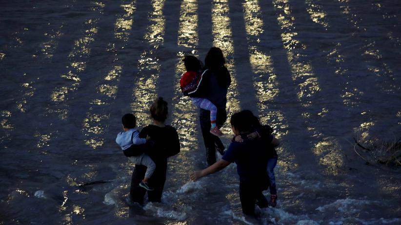 Migration: Drei Frauen mit Kindern auf ihren Armen versuchen den Rio Grande zu überqueren, um in den USA Asyl beantragen zu können.