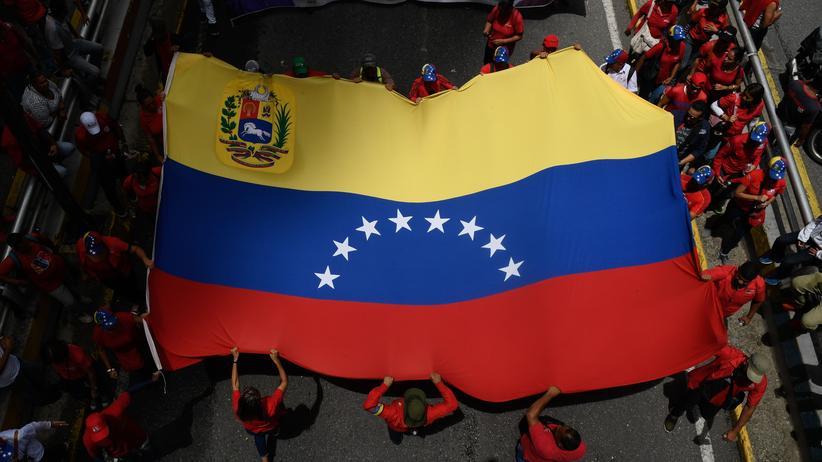 Venezuela: Unterstützer des venezolanischen Präsidenten Nicolás Maduro tragen eine Landesflagge bei einer regierungsfreundlichen Kundgebung in Caracas.