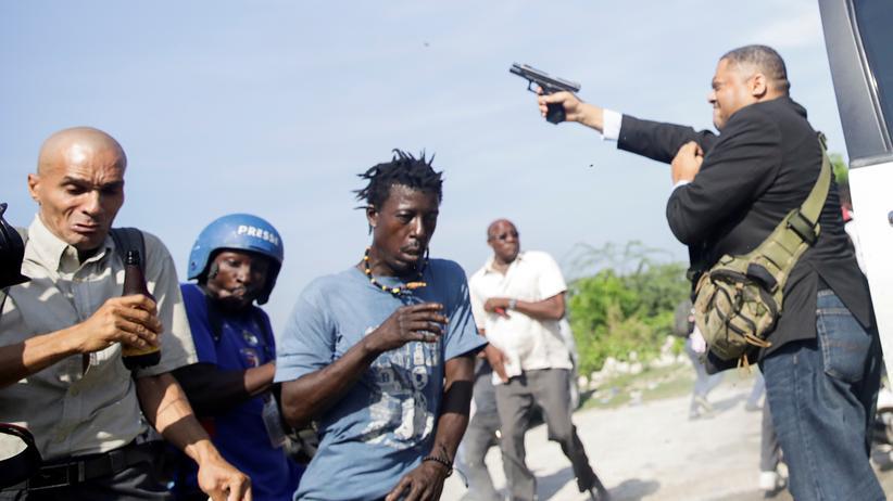 Haiti: Demonstrierende rennen davon, als Haitis Senator Jean Marie Ralph Féthière (PHTK) auf dem Parkplatz des Parlaments seine Pistole zieht.