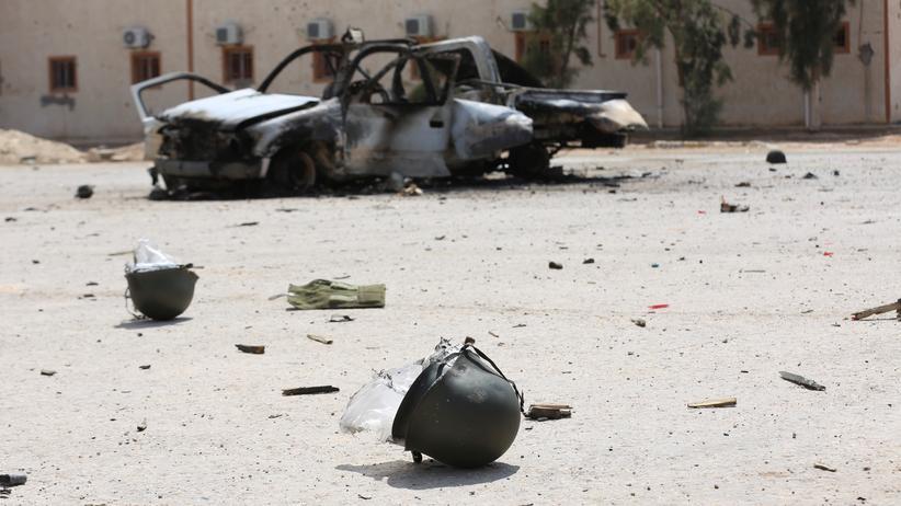 Migration: Ein Autowrack und Helme liegen nach einem Kampf zwischen verfeindeten Gruppen auf der Straße.