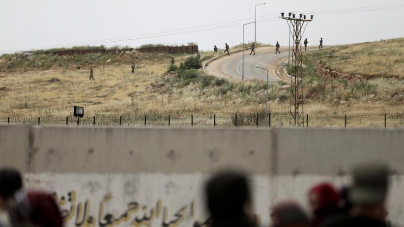 Syrien: Syrerinnen und Syrer (Vordergrund) beobachten türkische Soldaten auf der anderen Seite der Grenzmauer.