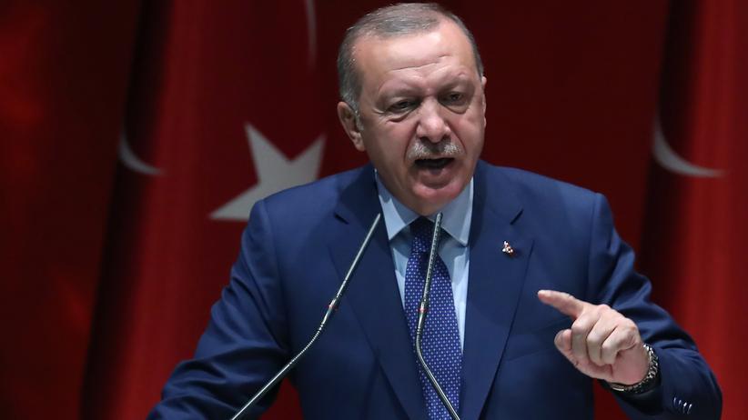 Erdogan mit erhobenem Zeigefinger am Rednerpult vor türkischer Flagge
