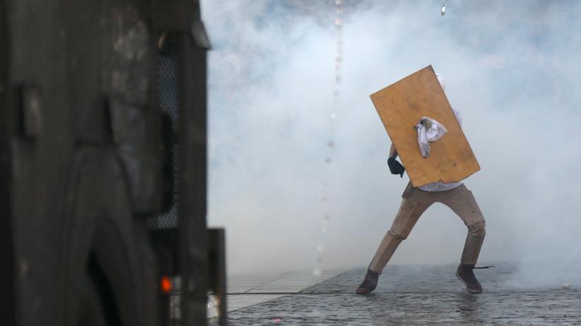 Chile: Ein Demonstrant versucht sich mit einem Holzschild vor Wasserwerfern der Sicherheitskräfte in Santiago zu schützen.