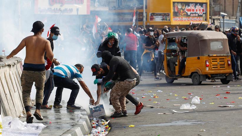 Irak: Demonstrierende in Bagdad versuchen, das aufsteigende Tränengas mit Wasser zu binden.