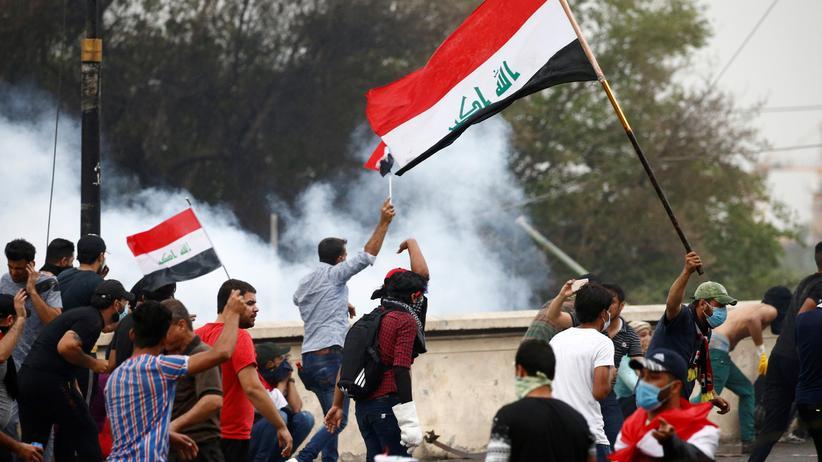 Irak: Demonstrierende in Bagdad fliehen vor aufsteigendem Tränengas.
