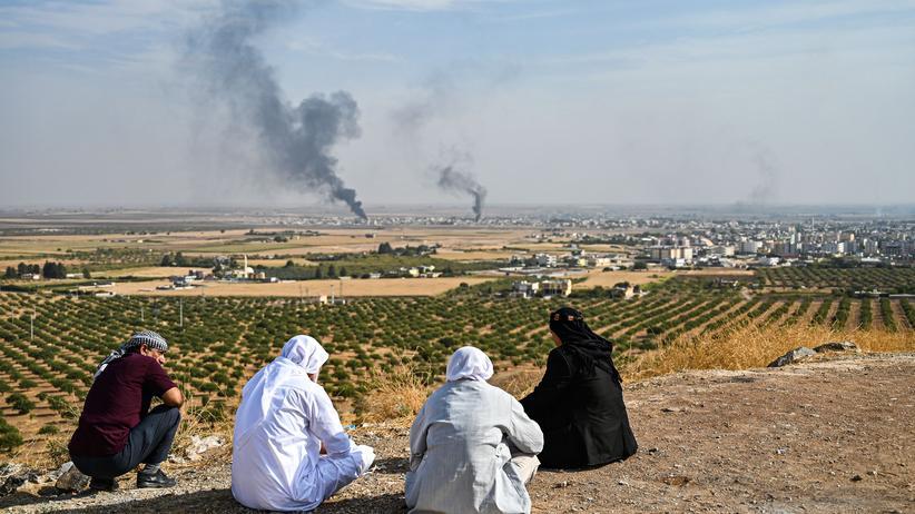 Nordysrien: Menschen beobachten, wie Rauch aus der syrischen Grenzstadt Ras al-Ain aufsteigt. Laut den Vereinten Nationen flohen bisher etwa 100.000 Menschen vor den Kämpfen.