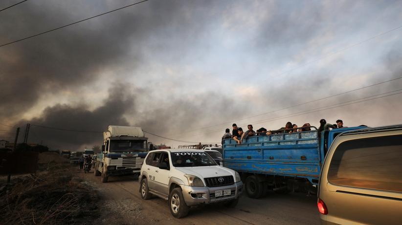 Nordsyrien: Zivilistinnen und Zivilisten fliehen auf der Ladefläche eines Trucks aus der Stadt Ras al Ain im nordsyrischen Grenzgebiet. Die Türkei hat in der Region eine Militäroffensive gegen kurdische Milizen gestartet.