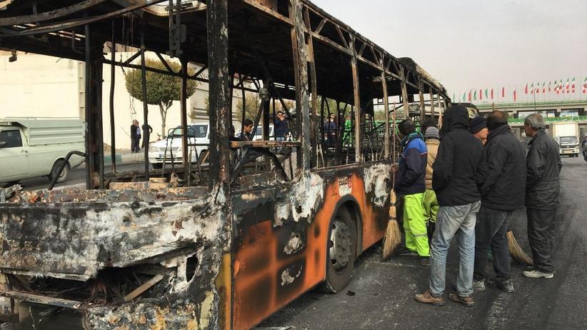 Benzinpreiserhöhung: In der iranischen Stadt Isfahan stehen die Überreste eines Busses, der von Demonstrierenden angezündet wurde.