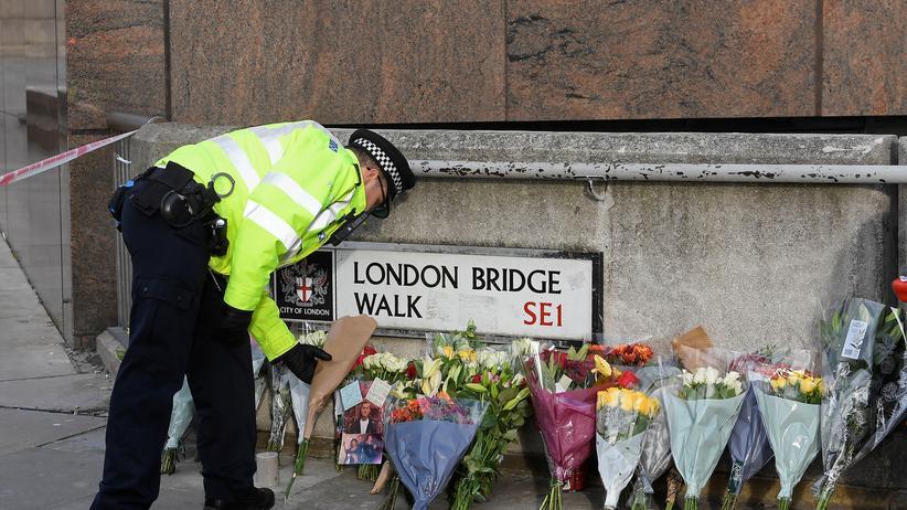 London Bridge: Ein Polizist legt Blumen nahe der Stelle ab, in der ein Terrorist zwei Passanten erstochen hat.