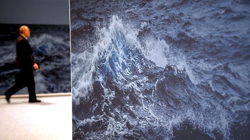 Weltklimakonferenz: Ein Mann läuft bei der UN-Klimakonferenz an einem Bild einer riesigen Welle vorbei.