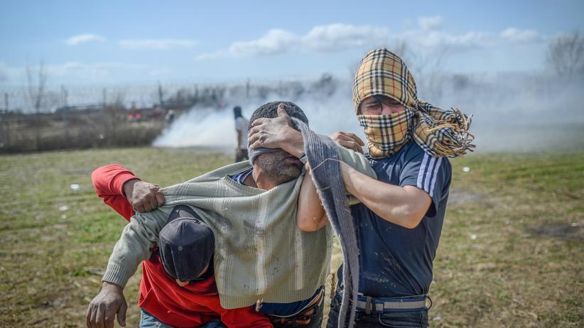 EU-Grenze: Zwei Migranten stützen einen Mann, der von Tränengas getroffen wurde. Mehrere Geflüchtete hatten versucht, die Grenze zu Griechenland einzureißen.