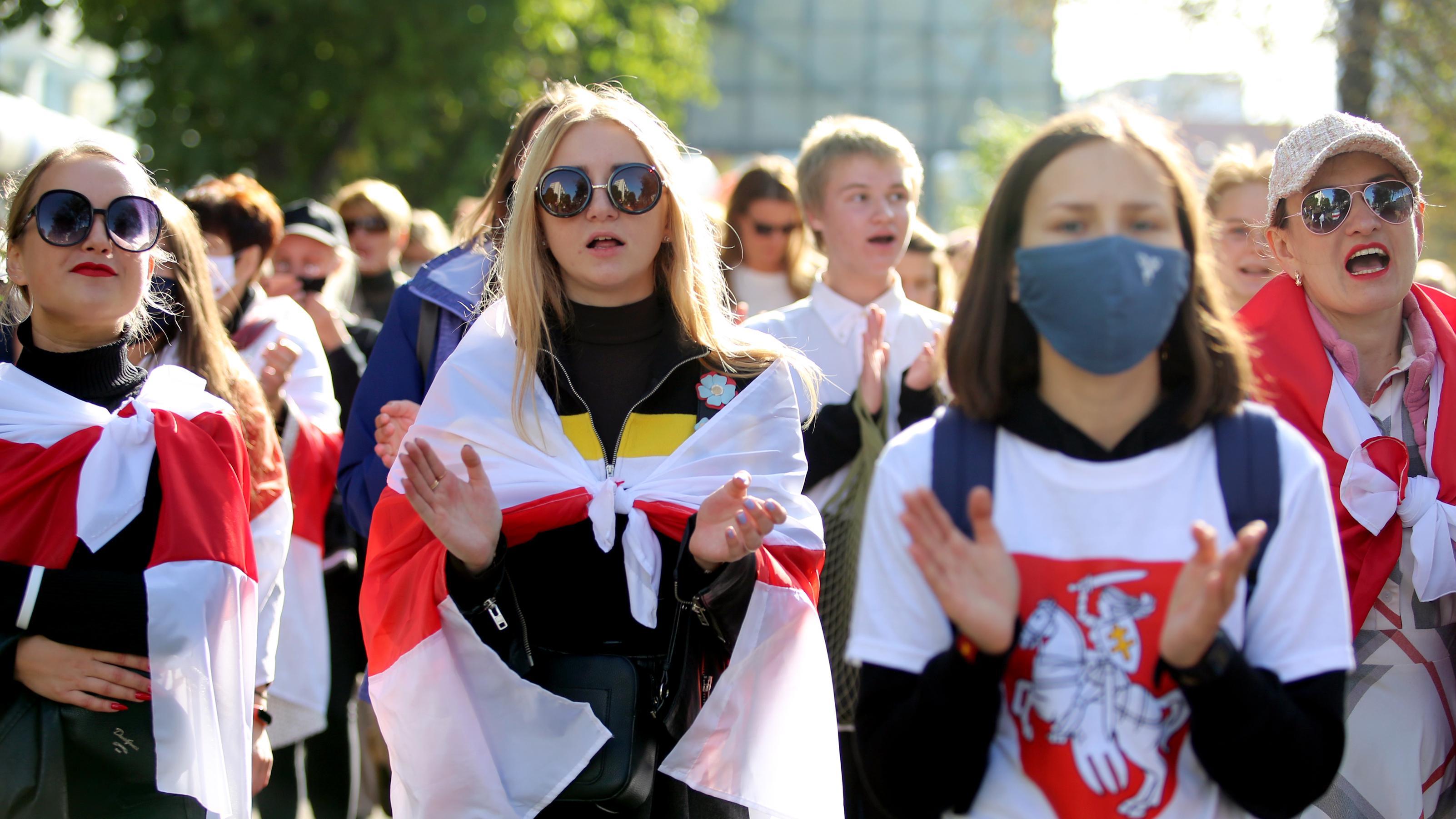 Proteste in Minsk: Demonstrantinnen protestieren gegen den belarussischen Präsidenten Alexander Lukaschenko. Sie tragen die ehemaligen weiß-rot-weißen Flaggen von Belarus über die Schulter gehängt.