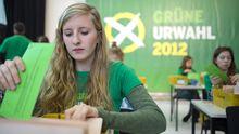 Eine Helferin öffnet Briefe mit Stimmen der Grünen-Urwahl.