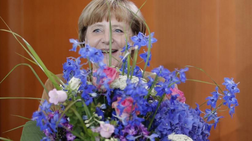 Bundeskanzlerin Angela Merkel erhält zu ihrem 59. Geburtstag am 17. Juli 2013 einen Blumenstrauß.