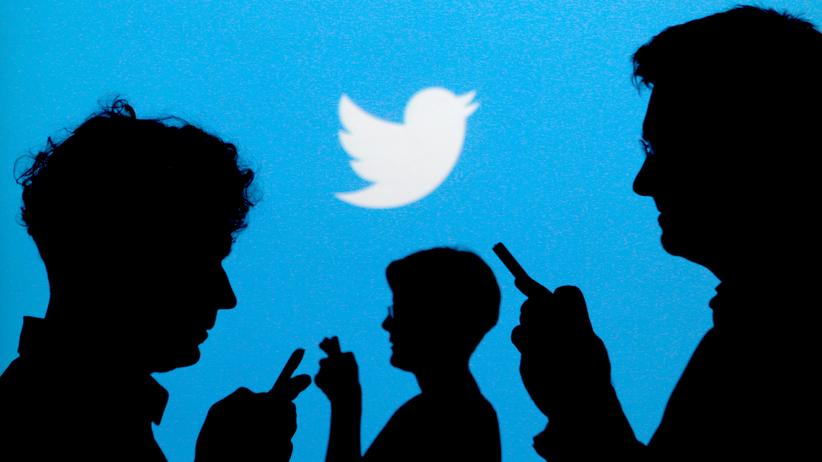 Datenschutz: Menschen halten Smartphones, dahinter das Logo von Twitter