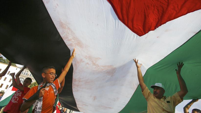 Palästinenser in Berlin: Menschen halten eine gigantische palästinensische Fahne in Berlin in die Höhe.
