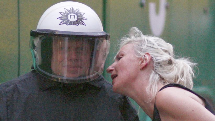 Demonstrationsrecht: Eine Frau ruft einem Polizisten ins Ohr.
