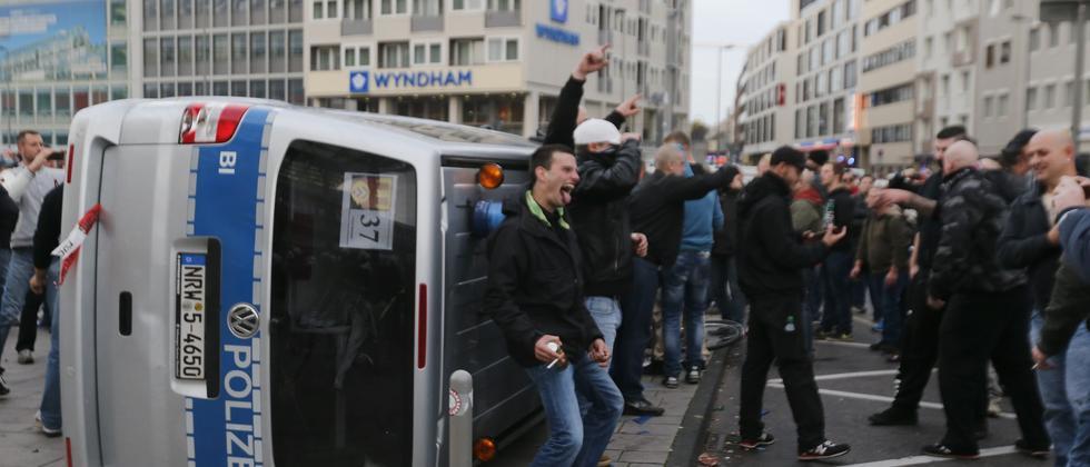 Hooligans in Köln warfen ein Polizeifahrzeug um.