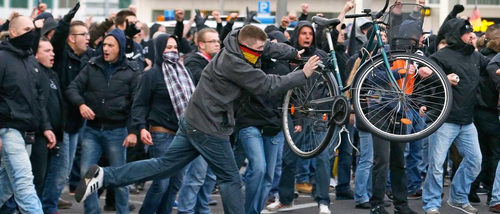 Ein Demonstrationsteilnehmer in Köln wirft mit einem Fahrrad.
