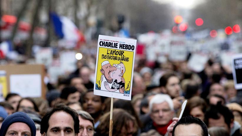 """Ein Demonstrant hält in Paris das Titelblatt einer Ausgabe der Satirezeitung """"Charlie Hebdo"""" hoch."""