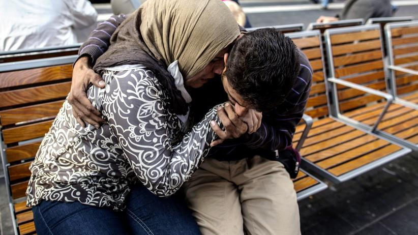 Flüchtlingskrise: Ihab, 30, a Syrian migrant from Deir al-Zor, kisses the hands of his mother Huda, 48, as he and his family arrive at the railway station in Lubeck, Germany September 18, 2015. Picture taken September 18, 2015. REUTERS/Zohra Bensemra