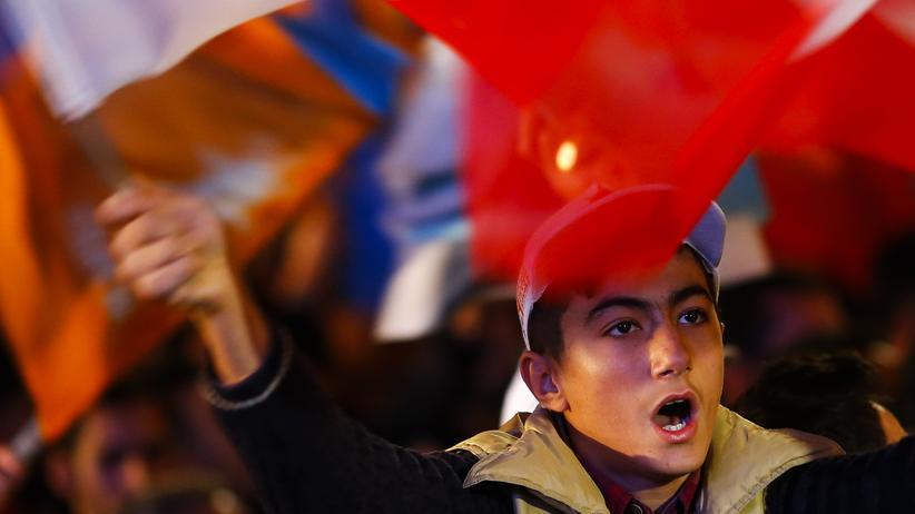 Türkei: Menschen schwingen vor dem Parteisitz der AKP in Ankara die türkische Flagge.