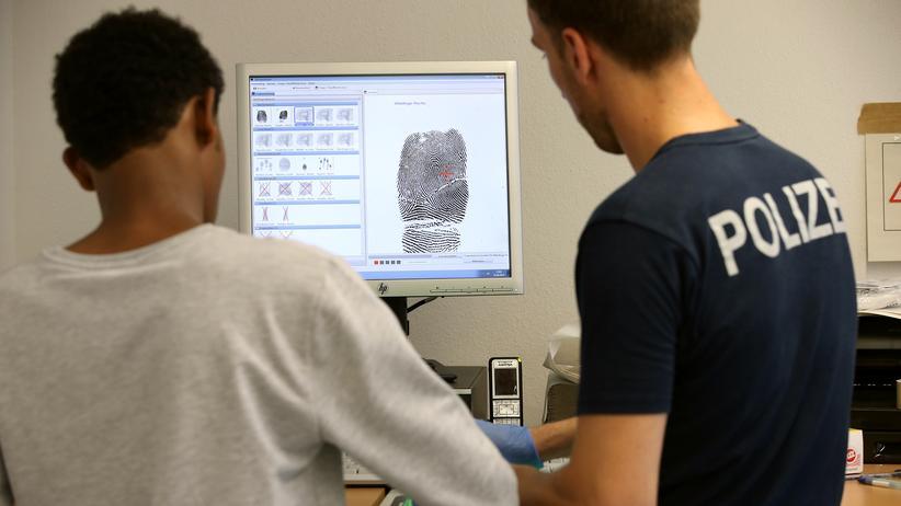 Flüchtlinge: Ein Polizist in Rosenheim nimmt einen Fingerabdruck von einem Flüchtling