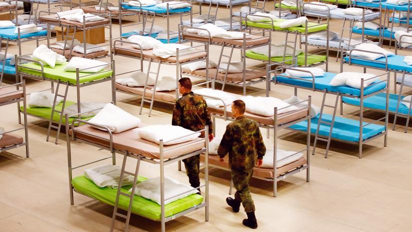 Bundeswehr: Soldaten der Bundeswehr errichten in einer Sporthalle eine Flüchtlingsunterkunft.