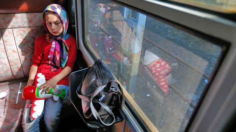Ein geflüchtetes Kind sitzt in einem Zug gen Österreich.
