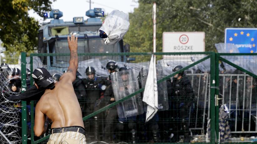 Populismus gegen Flüchtlinge: So sieht eine streng bewachte europäische Grenze aus: Übergang beim ungarischen Röszke. Ein Flüchtling wirft einen Beutel auf die Beamten, nachdem diese Wasserwerfer und Reizgas eingesetzt hatten, um die Migranten von der versuchten Einreise abzuhalten.
