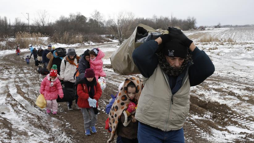 Flüchtlingskrise : Flüchtlinge gehen über ein gefrorenes Feld nahe des serbischen Ortes Miratovac. Zuvor hatten sie auf der Balkanroute die mazedonische Grenze überquert.