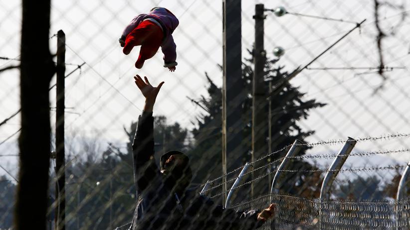Flüchtlingspolitik: Ein Flüchtling spielt mit seinem Baby an der griechisch-mazedonischen Grenze, während sie umzingelt von Zäunen auf Einlass nach Mazedonien warten.