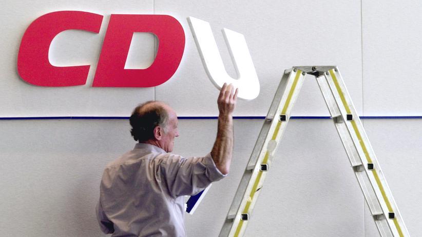 Ein Mann entfernt das Logo der CDU von einer Wand.