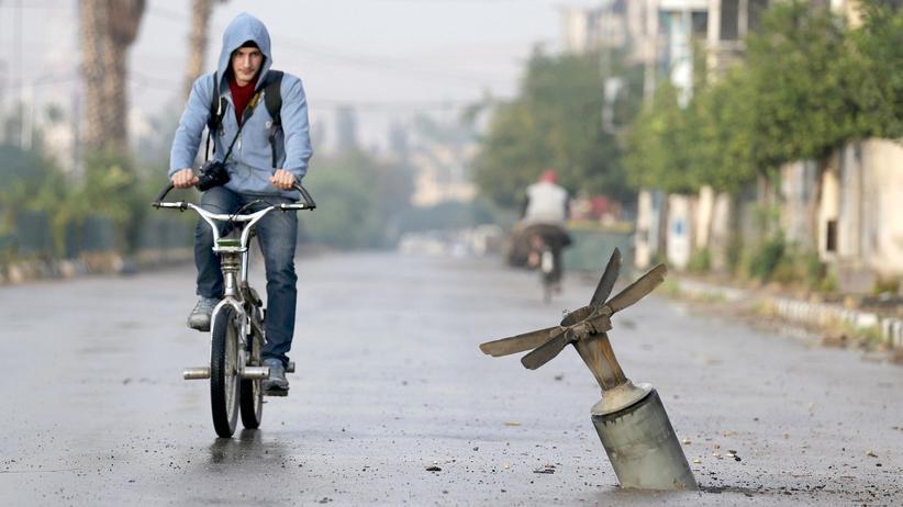 Waffengeschäfte: In der syrischen Hauptstadt Damaskus fährt ein Radfahrer im November 2015 an einem Bombenmantel vorbei, der laut Aktivisten Streumunition transportierte.