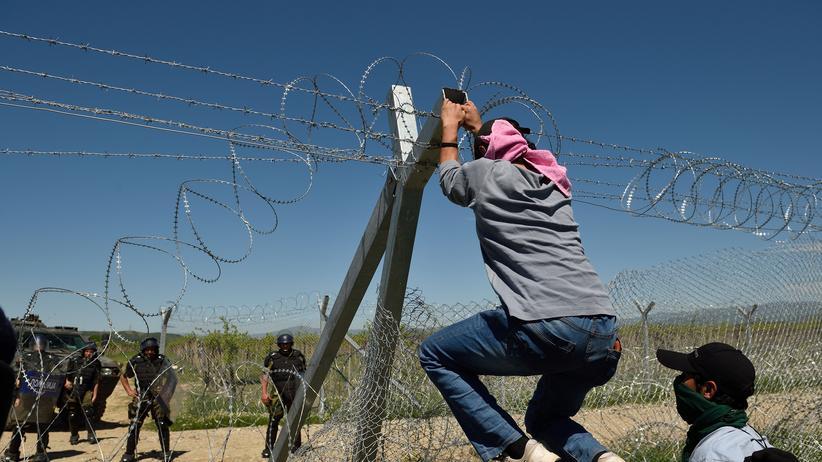 Migration: Junge Flüchtlinge versuchen den Grenzzaun zwischen Griechenland und Mazedonien einzureißen. Beobachtet werden sie von mazedonischen Sicherheitskräften.