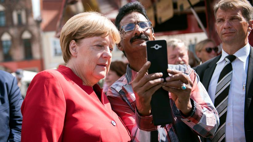 Flüchtlingspolitik: Angela Merkel macht beim Wahlkampf in Mecklenburg-Vorpommern auf einem Marktplatz in Greifswald ein Selfie mit einem ausländischen Besucher.