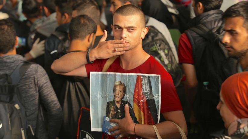 Flüchtlingspolitik: Ein syrischer Flüchtling mit einem Bild von Bundeskanzlerin Angela Merkel bei seiner Ankunft am Münchner Hauptbahnhof (2015)