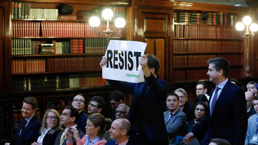 Wissenschaftler: Ein Umweltaktivist hält Myron Ebell, damals noch Chef des Übergangsteams der US-Umweltagentur EPA, am 1. Februar in Brüssel ein Schild entgegen, das zum Widerstand aufruft. Ebell ist nicht im Bild.