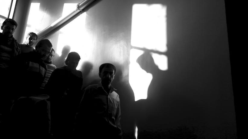 Berlin: Häftlinge gehen 2015 eine Treppe in einem syrischen Gefängnis in Homs herunter.
