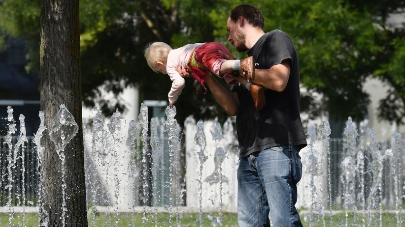 Ein Vater zeigt seinem Kind in Berlin einen Springbrunnen.