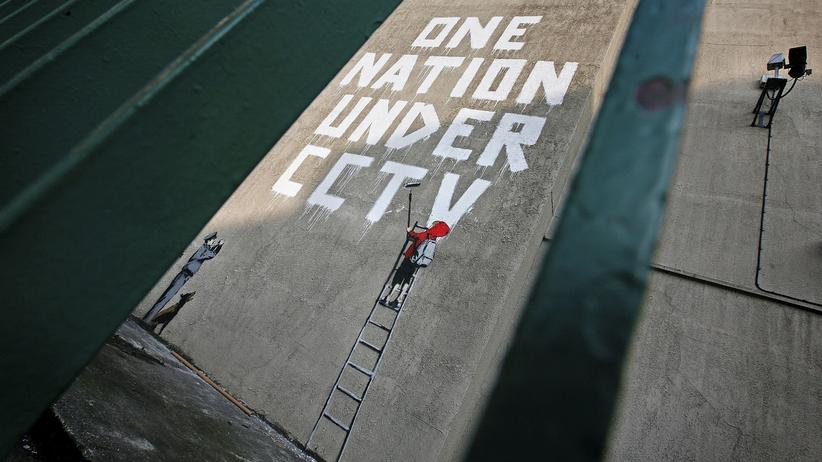 """Theresa May: Der Graffitikünstler Banksy hat eine Hauswand in London bemalt: """"Eine Nation unter Videoüberwachung"""" schreibt ein kleines Kind, das dabei von einem Wachmann beobachtet wird."""