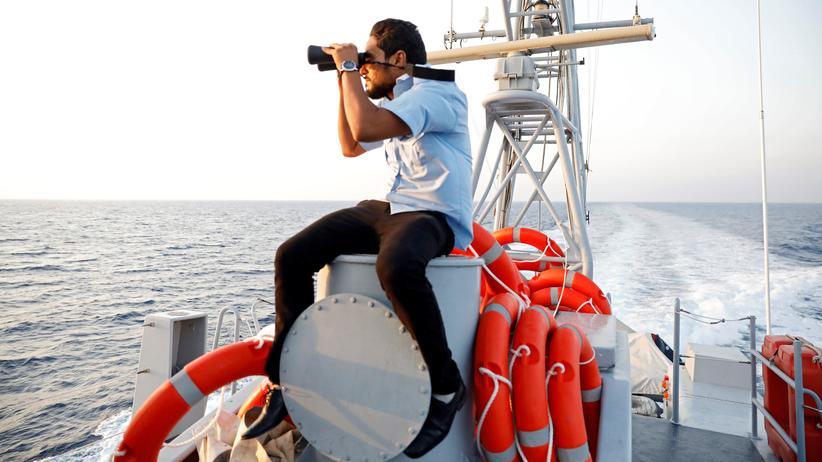 Flüchtlinge: Ein Mitarbeiter der libyschen Küstenwache hält vor Tripolis mit einem Fernglas nach Migranten Ausschau.