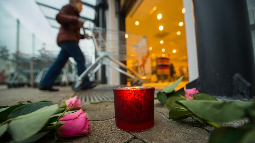 Kandel: Eine Kerze und Blumen liegen vor dem Drogeriemarkt, in dem ein junger Flüchtling seine gleichaltrige Ex-Freundin erstochen haben soll.