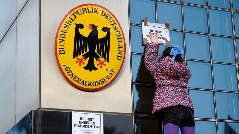 """Festnahme von Carles Puigdemont: """"Befreit unseren Präsidenten"""": In Barcelona klebt eine Demonstrantin einen Zettel auf die Vertretung Deutschlands."""