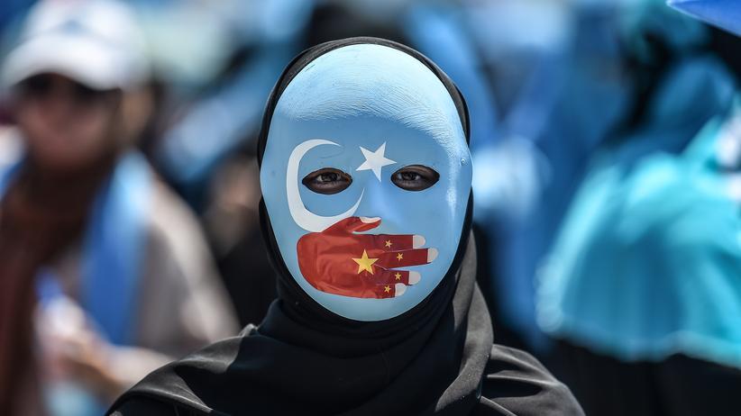 Menschenrechte: Ein Demonstrant trägt eine Maske in den Farben der uigurischen Flagge.