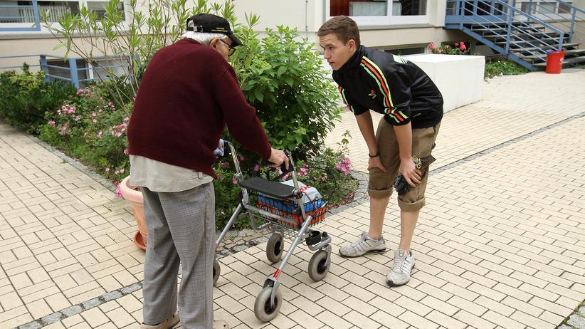 Engagement: Ein junger Freiwilligendienstleister spricht mit dem Bewohner einer Altenresidenz.
