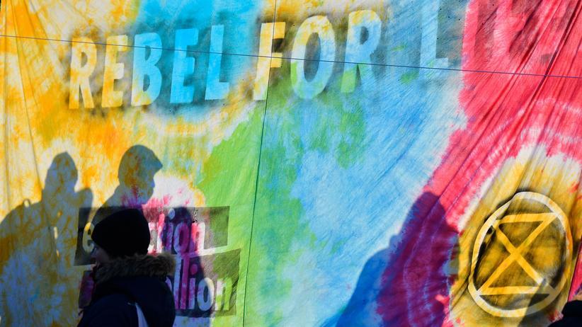 Klimapolitik: Extinction-Rebellion-Protestierende, zu sehen als Schatten hinter einem Banner, am Montag in Berlin